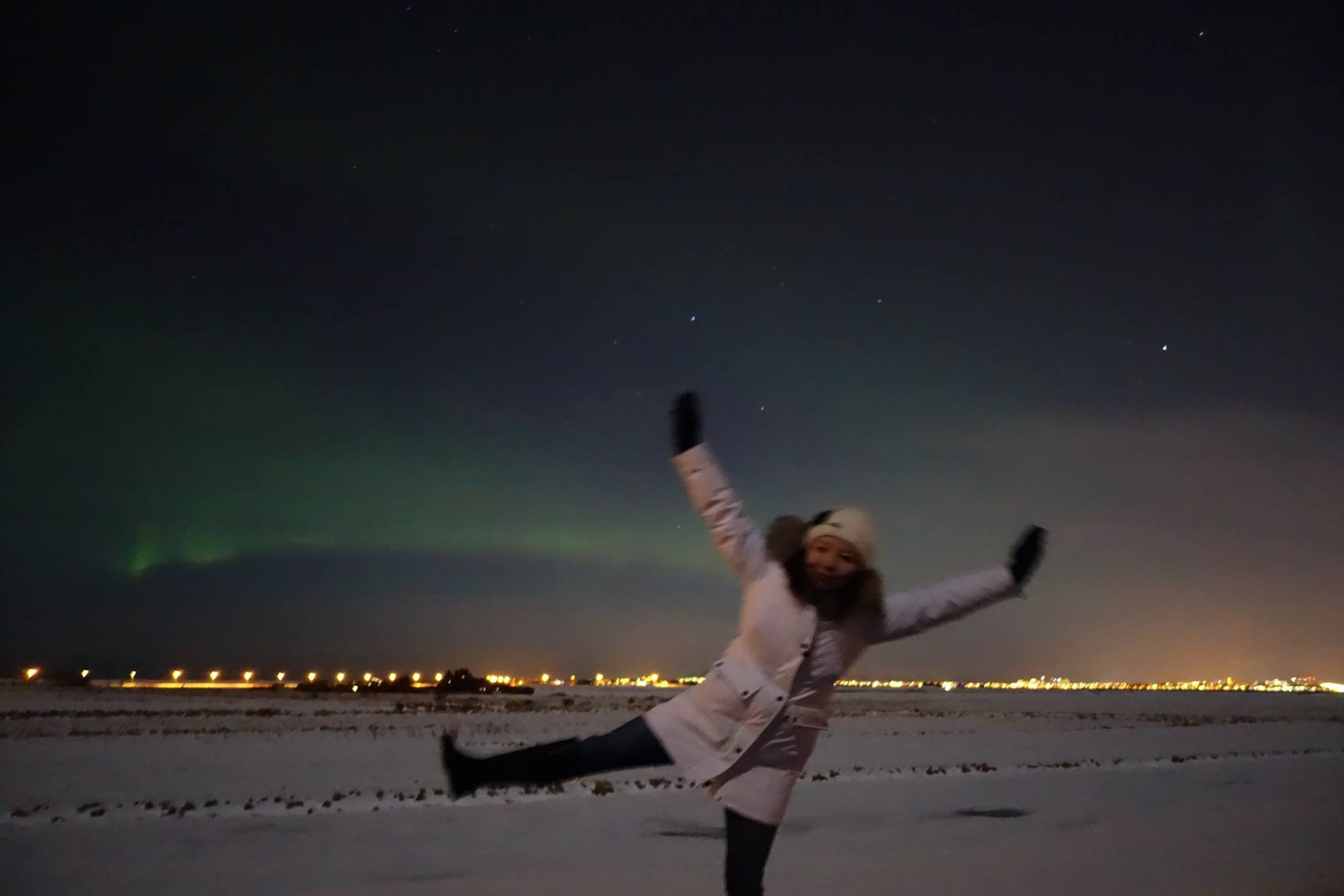 Jen in Iceland, dancing in front of an aurora